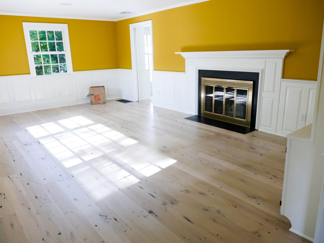 Happily Eva After home in Connecticut with light wood floors, mustard walls and white judge's paneling around the wood burning fireplace in the formal living room.