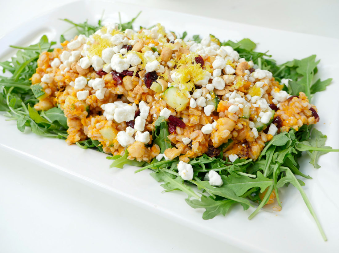 Happily Eva After Autumn Farro Salad with Sweet Potato, Cucumber, Chickpeas, cranberries, goat cheese, cashews, arugula, and lemon zest phtographed in a marble kitchen with a blue shibori dyed tea towel and sunflowers