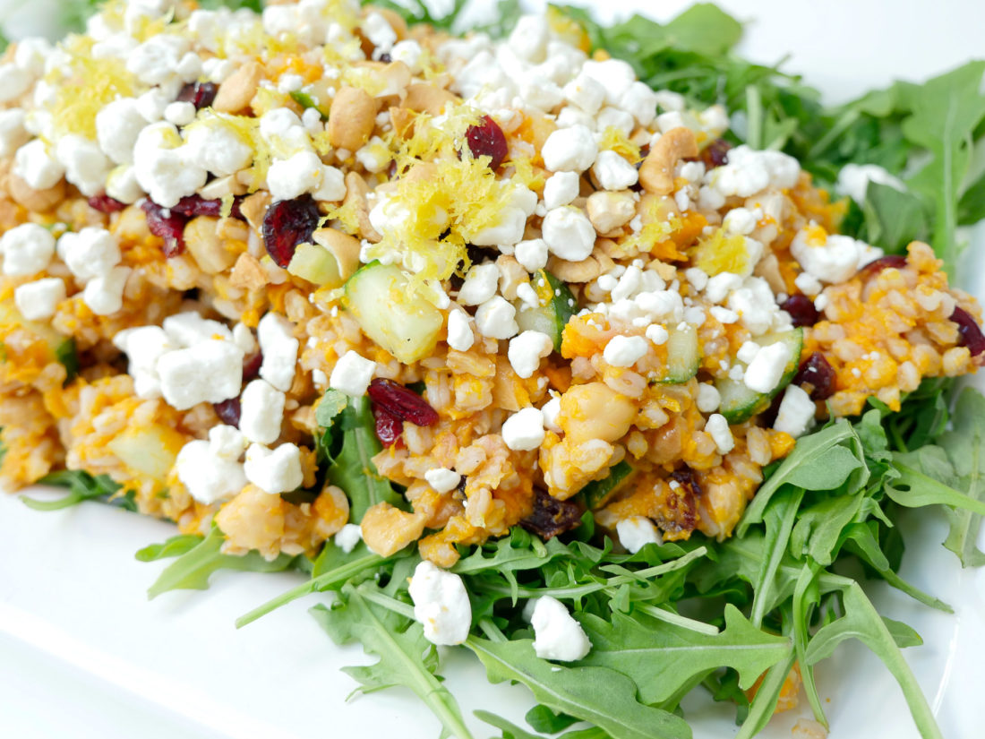 Happily Eva After Autumn Farro Salad with Sweet Potato, Cucumber, Chickpeas, cranberries, goat cheese, cashews, arugula, and lemon zest phtographed in a marble kitchen