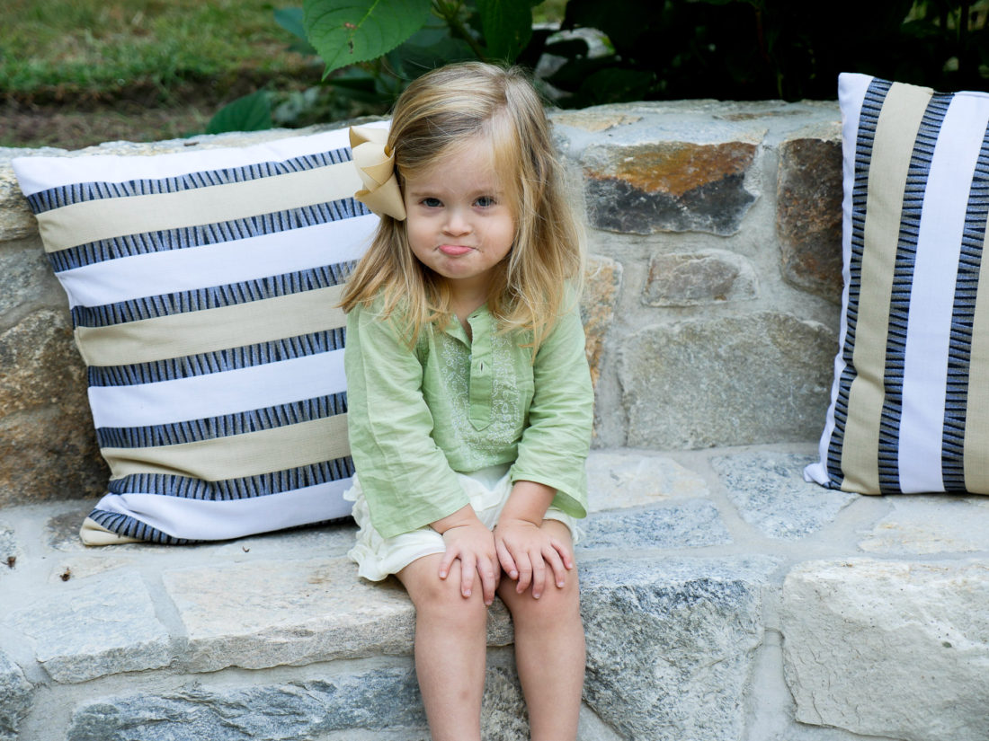 Marlowe Martino in a green tunic and white frilled shorts sitting outdoors on a stone bench with striped pillows