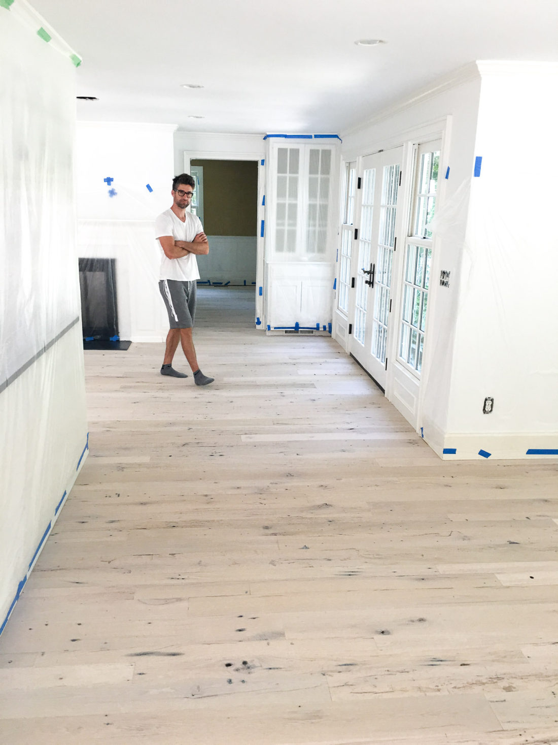 Kyle Martino walking on refinished light wood floors in his house in Connecticut