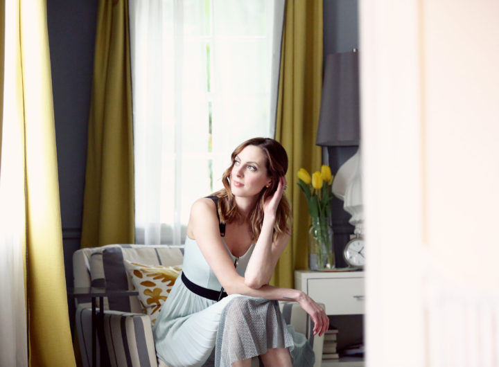 Eva Amurri Martino of the blog Happily Eva After wearing a pale blue dress and sitting on an armchair in the corner of the bedroom, looking out the window