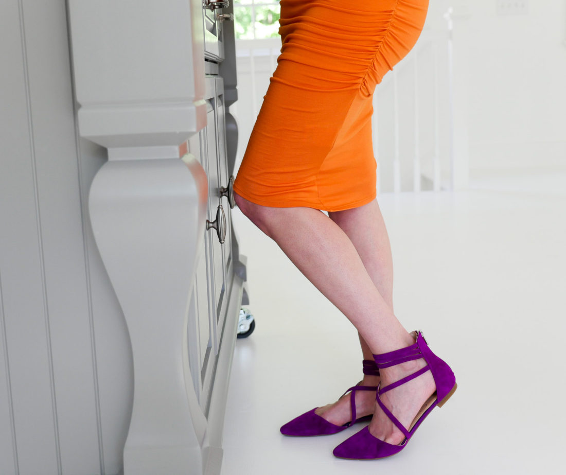 Eva Amurri Martino of lifestyle blog Happily Eva After wearing an orange maternity dress at 34 weeks pregnant and a pair of bright purple jessica simpson flats in her studio in connecticut