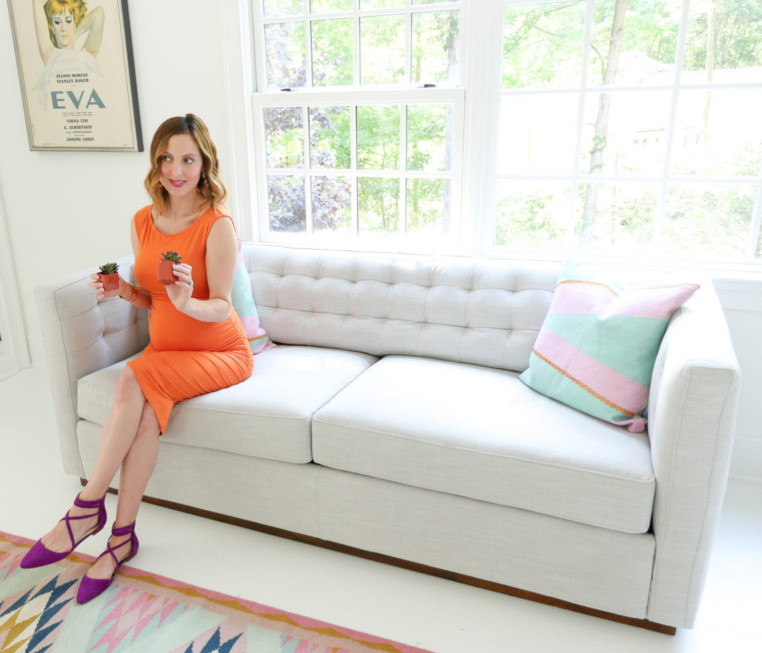 Eva Amurri Martino of lifestyle blog Happily Eva After sititng on the light grey couch in her studio in an orange maternity dress and purple jessica simpson flats