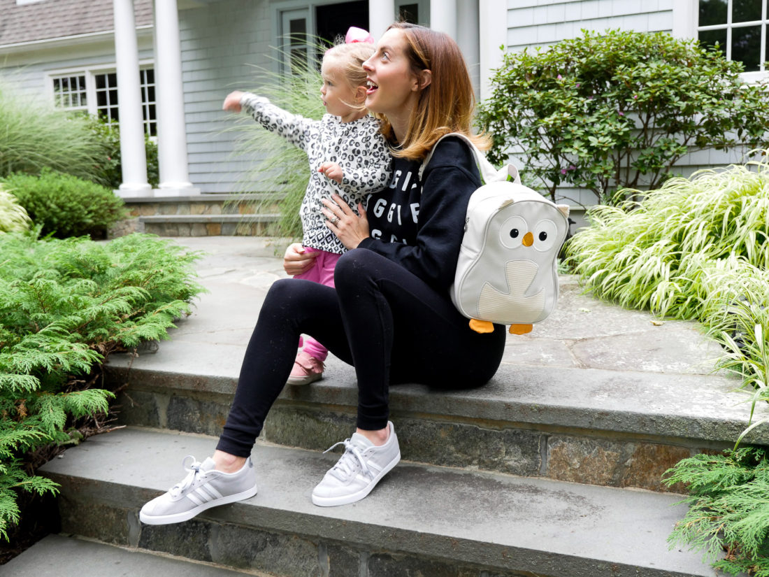 Eva Amurri Martino of lifestyle blog Happily Eva After with her daughter Marlowe sitting on their front steps together waiting to go off to school