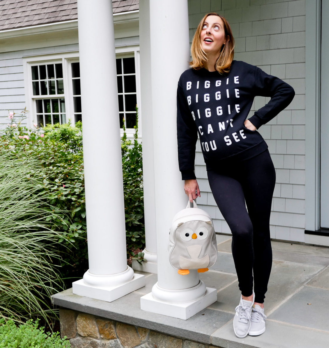 "Eva Amurri Martino of Lifestyle blog Happily Eva After at 34 weeks pregnant wearing black maternity leggings and a ""biggie biggie biggie can't you see"" sweatshirt and addidas neo courtset sneakers holding her daughter Marlowe's light grey owl backpack"