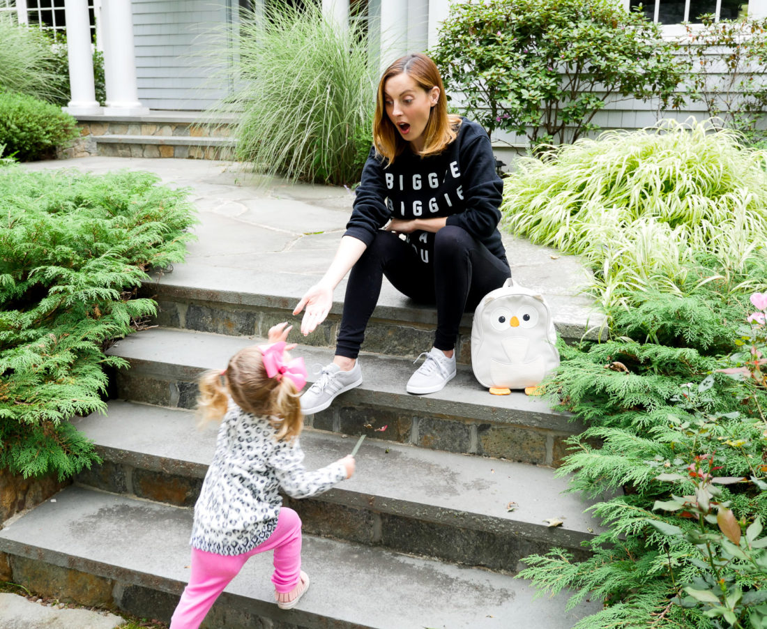 "Eva Amurri Martino of lifestyle blog Happily Eva After wearing black maternity leggings and a ""biggie biggie biggie can't you see"" sweatshirt with her daughter Marlowe on the steps of their home in connecticut"