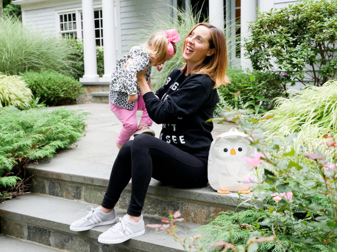 Eva Amurri Martino of lifestyle blog Happily Eva After sitting on the steps of her connecticut home wearing black maternity leggings, a blac sweatshirt, and light grey adidas sneakers, lifting her daughter Marlowe on to her lap