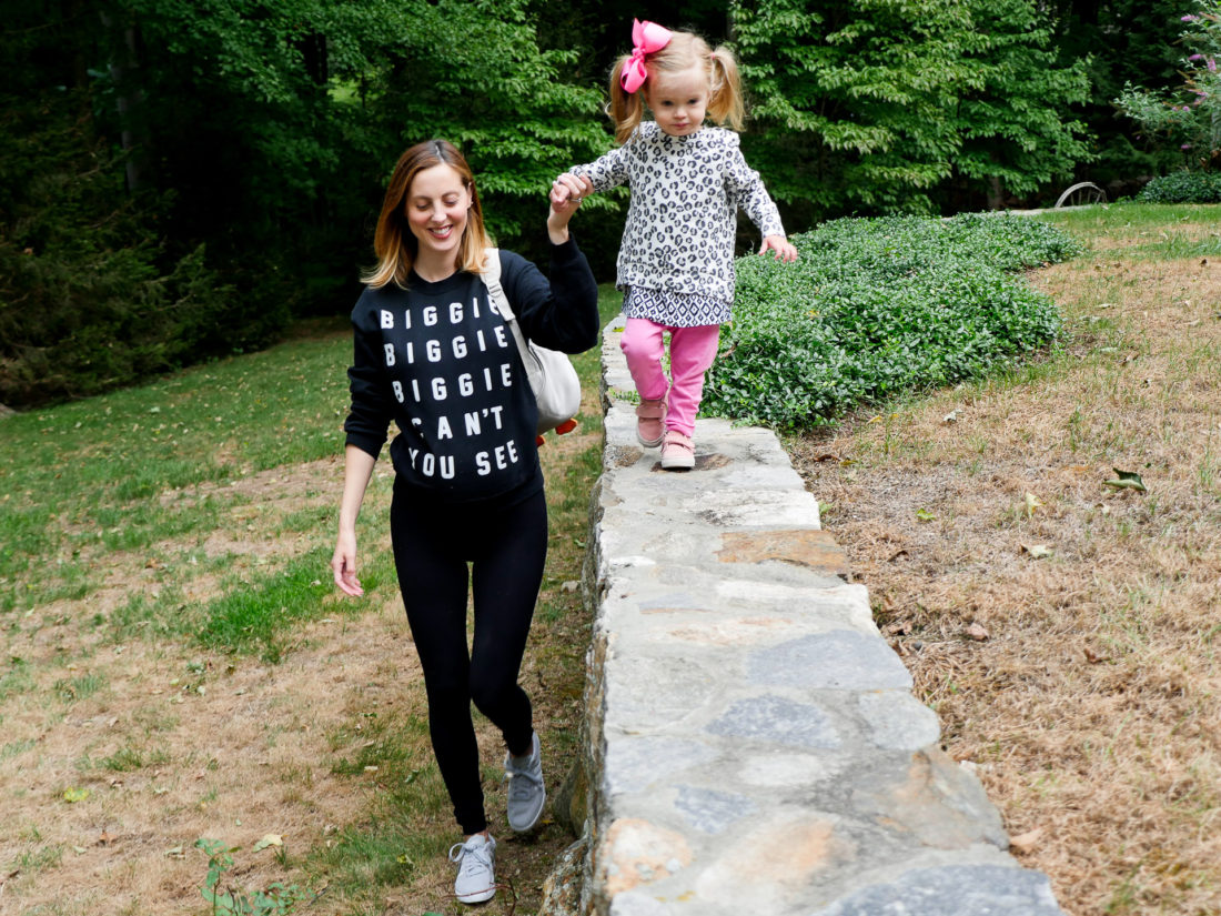 "Eva Amurri Martino of blog Happily Eva After wearing black leggings and a ""Biggie Biggie Biggie can't you see"" sweatshirt at thirty five weeks pregnant walking with her daughter marlowe wearing DSW adidas shoes"