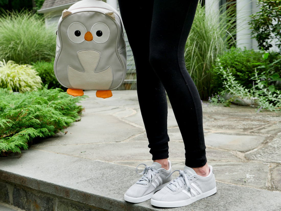 Eva Amurri Martino of lifestyle blog Happily Eva After wearing black maternity leggings and adidas sneakers holding her daughter's grey owl backpack