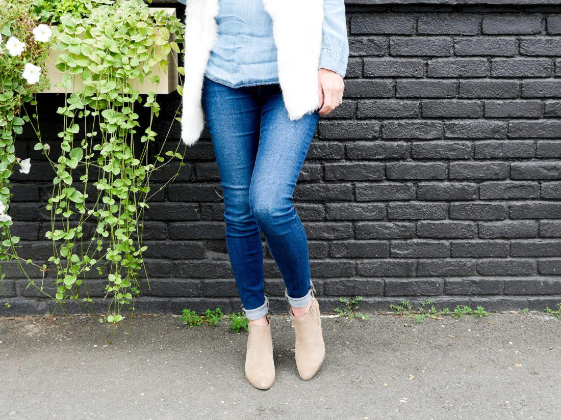 Eva Amurri Martino of Happily Eva After blog wearing maternity jeans, a chambray maternity top, a white fur vest, and tan colored fall boots standing against a dark grey wall
