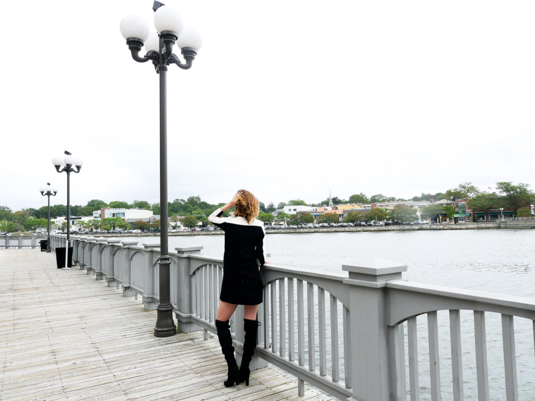 Eva Amurri Martino of lifestyle blog Happily Eva After wearing a mod black and cream shift dress and black over the knee boots facing out towards the water next to a lamp post