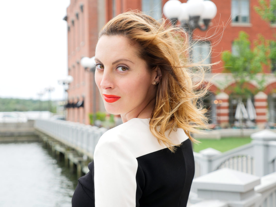 Eva Amurri Martino of lifestyle blog Happily Eva After wearing red lipstick and a cream and black dress standing at the waterfront in connecticut and looking back over her shoulder at the camera