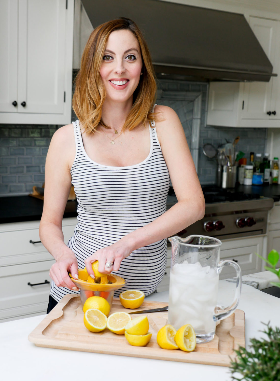 Eva Amurri Martino of lifestyle blog Happily Eva After squeezing lemons in her kitchen to make a hydrating laborade for her Home Birth