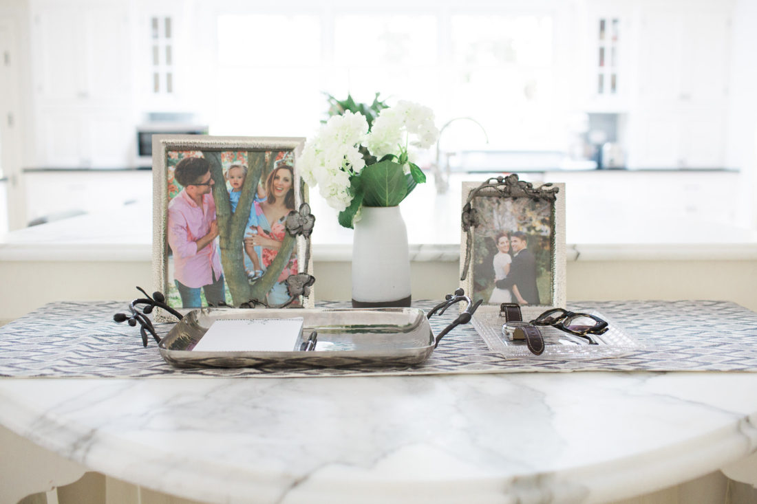 A close up of a tablescape with family photos in Michael Aram orchid motif frames on the marble kitchen island in Eva Amurri Martino's Connecticut home