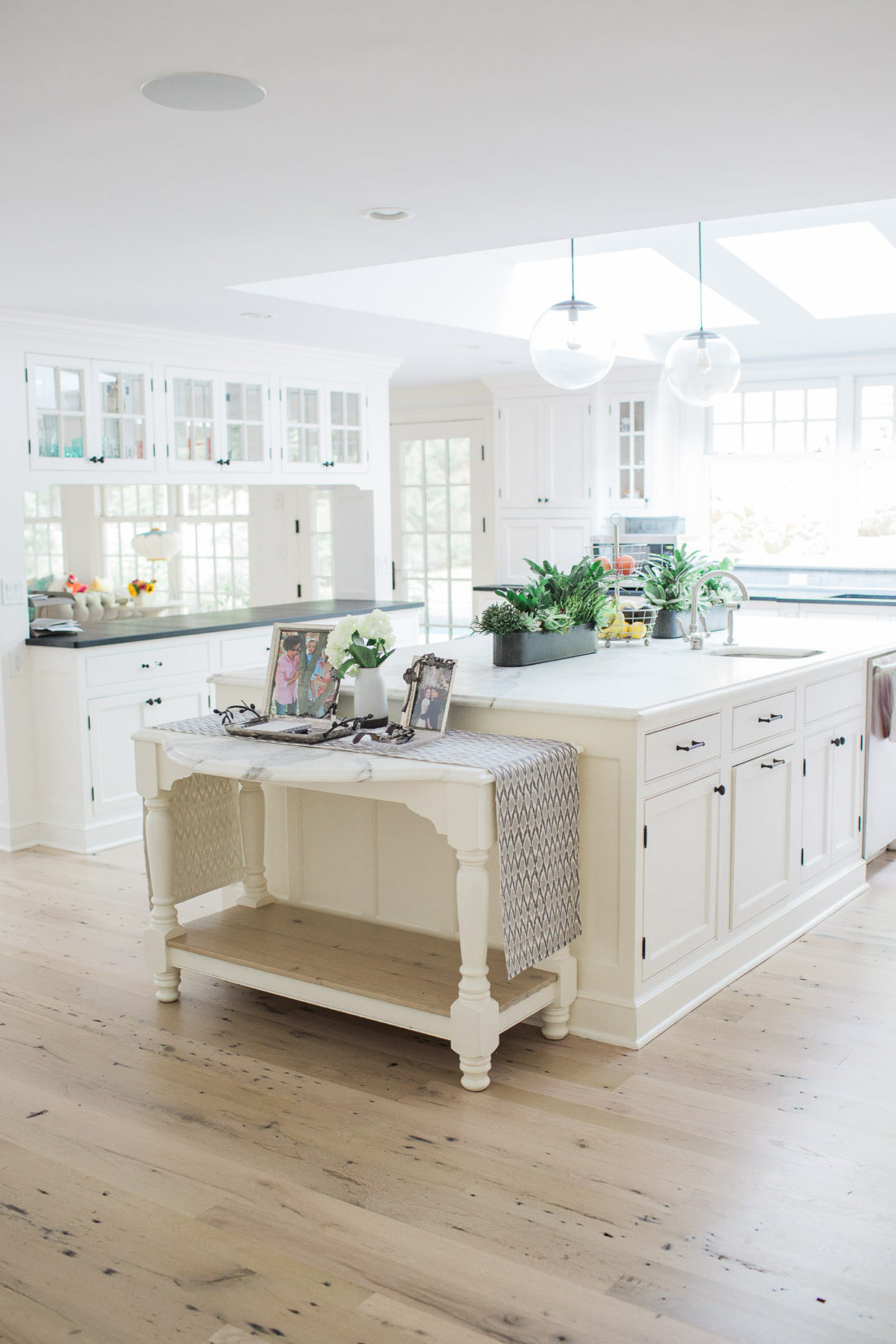 An entrance view of lifestyle blogger Eva Amurri Martino's white and bright kitchen in connecticut, featuring a huge marble island, skylights, and views of the pool and yard