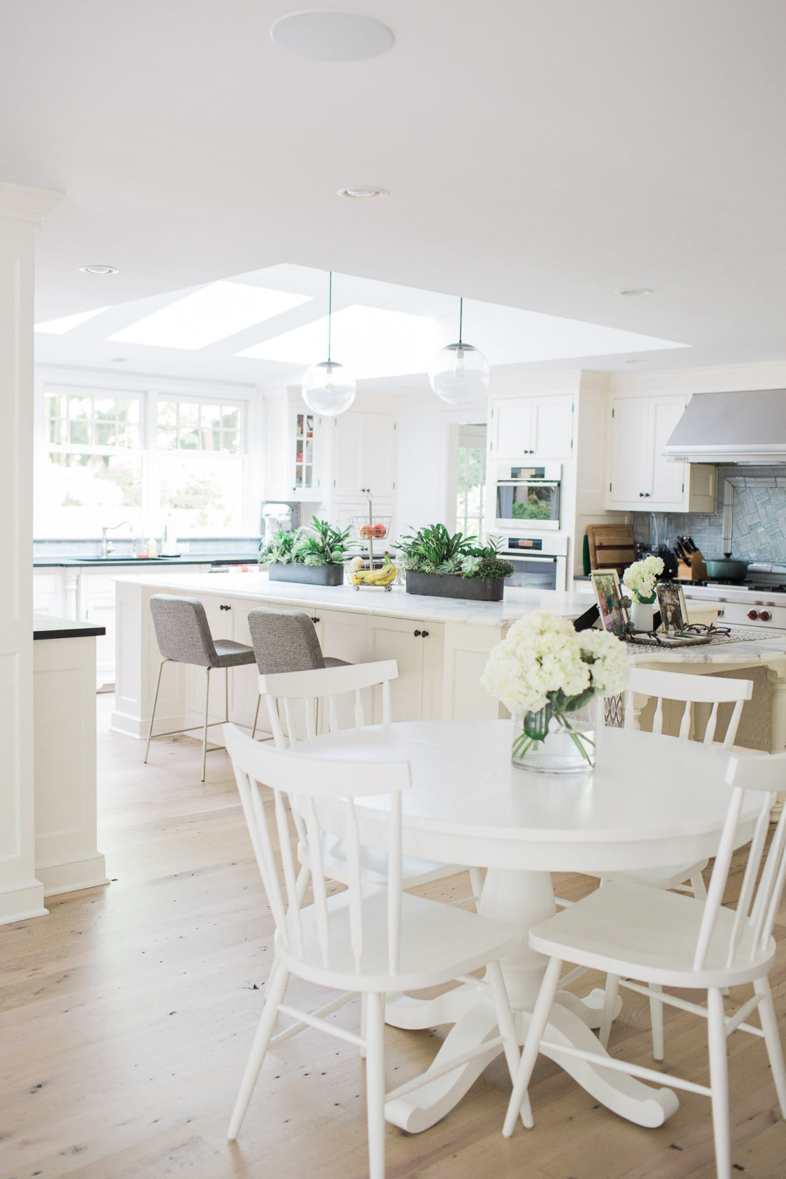 The bright, open, and airy kitchen of lifestyle blogger Eva Amurri Martino in connecticut featuring a big carrara marble island