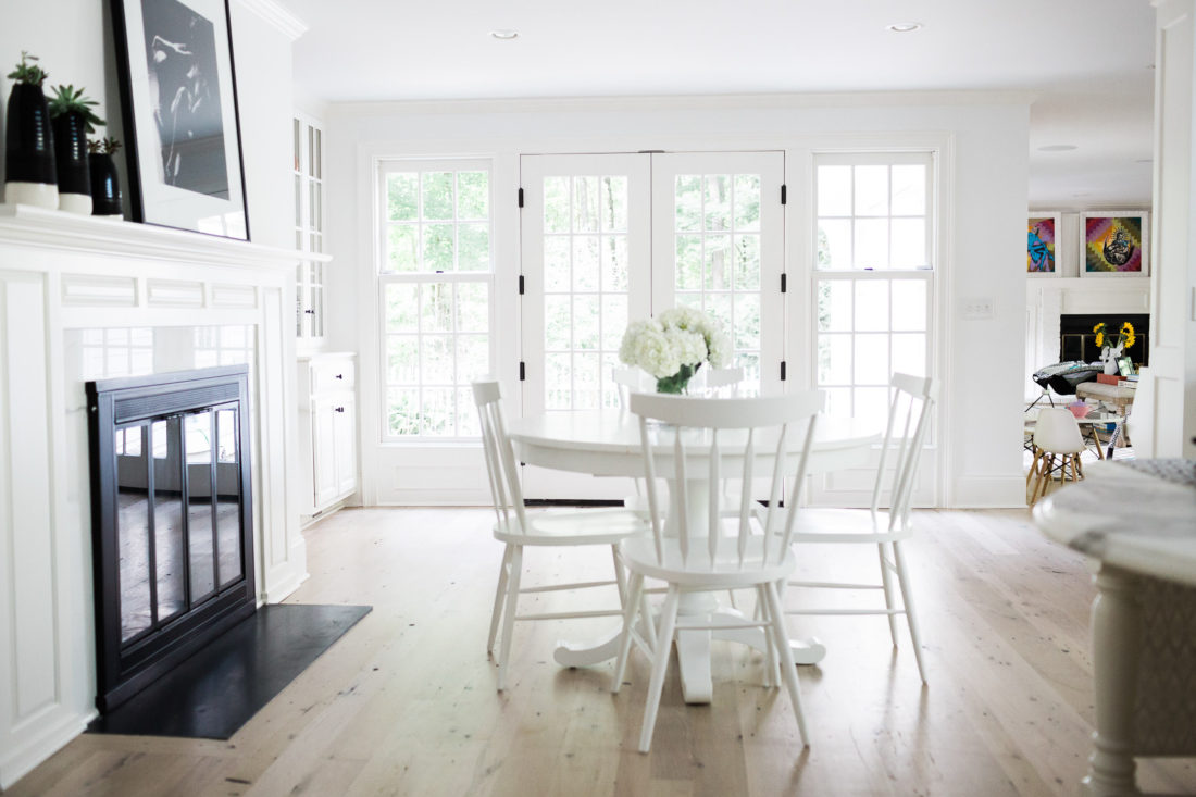 The kitchen table area of Eva Amurri Martino's Connecticut home, featuring a stark white kitchen table and white shaker chairs