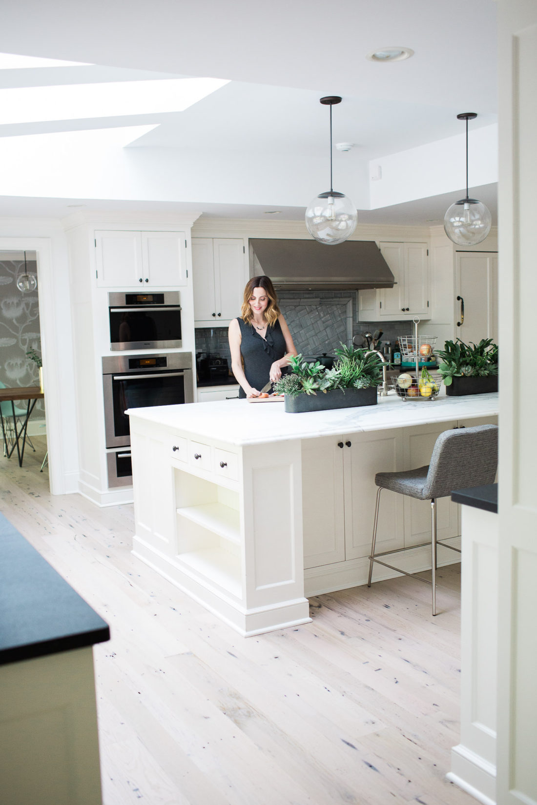 Eva Amurri Martin of lifestyle blog Happily Eva After chopping vegetables in her white and bright kitchen in connecticut with industrial accents