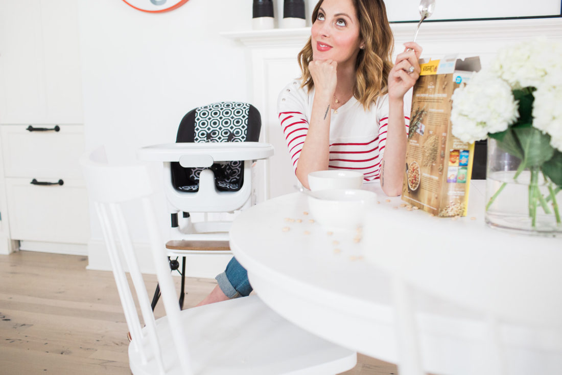 Eva Amurri Martino of Lifestyle blog Happily Eva After eating cereal at her white kitchen table next to the jonathan adler crafted by fisher price collection high chair