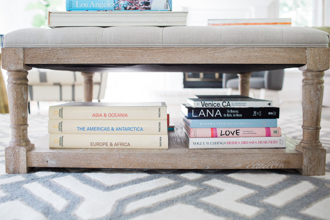 A close up of the array of coffee table books stacked under the coffee table ottoman in Eva Amurri Martino's family room of her connecticut home