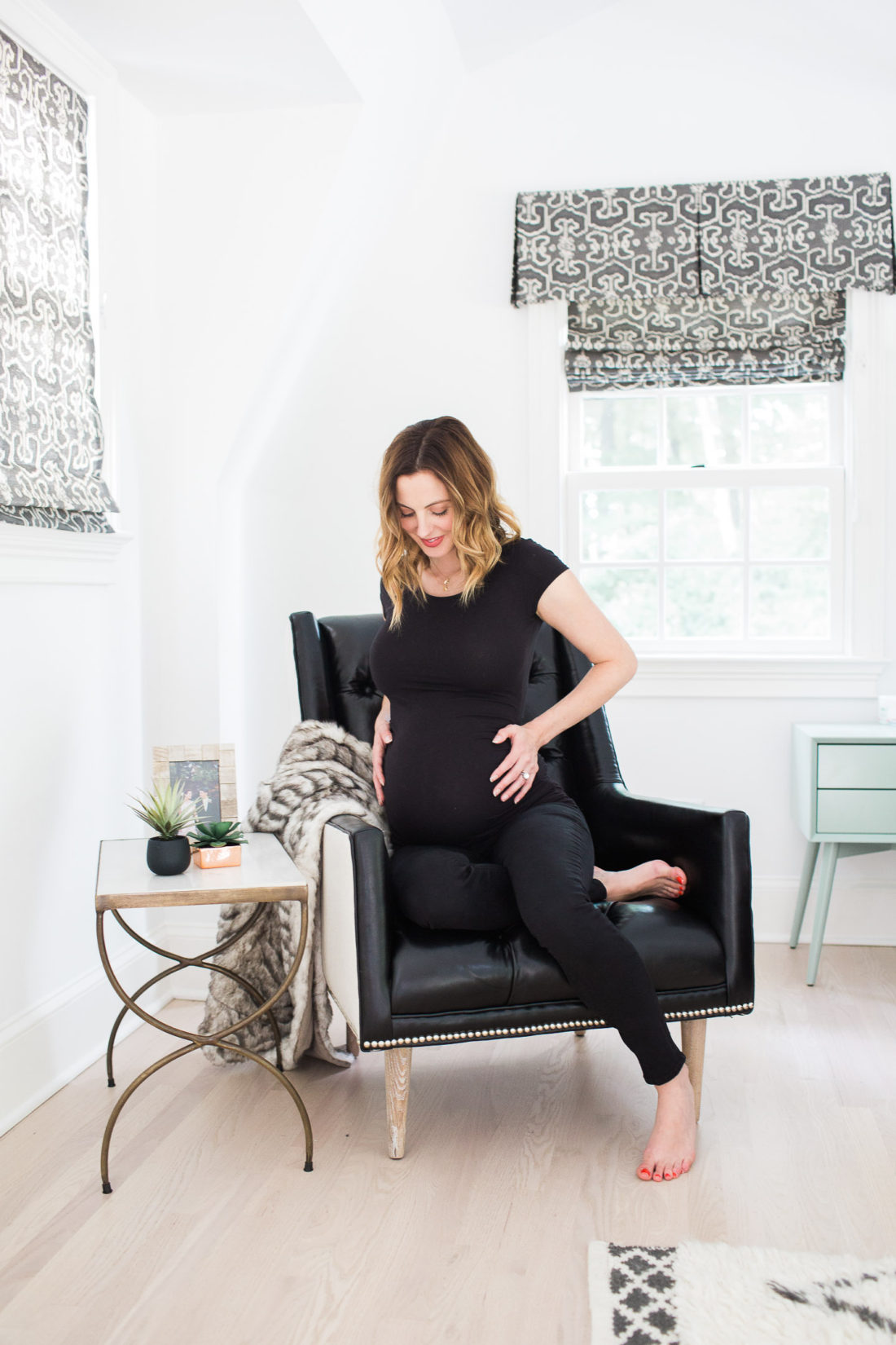 Eva Amurri Martino of lifestyle blog Happily Eva After cradling her 37 week bump while sitting in a black leather chair in her master bedroom next to a brass table and two succulents