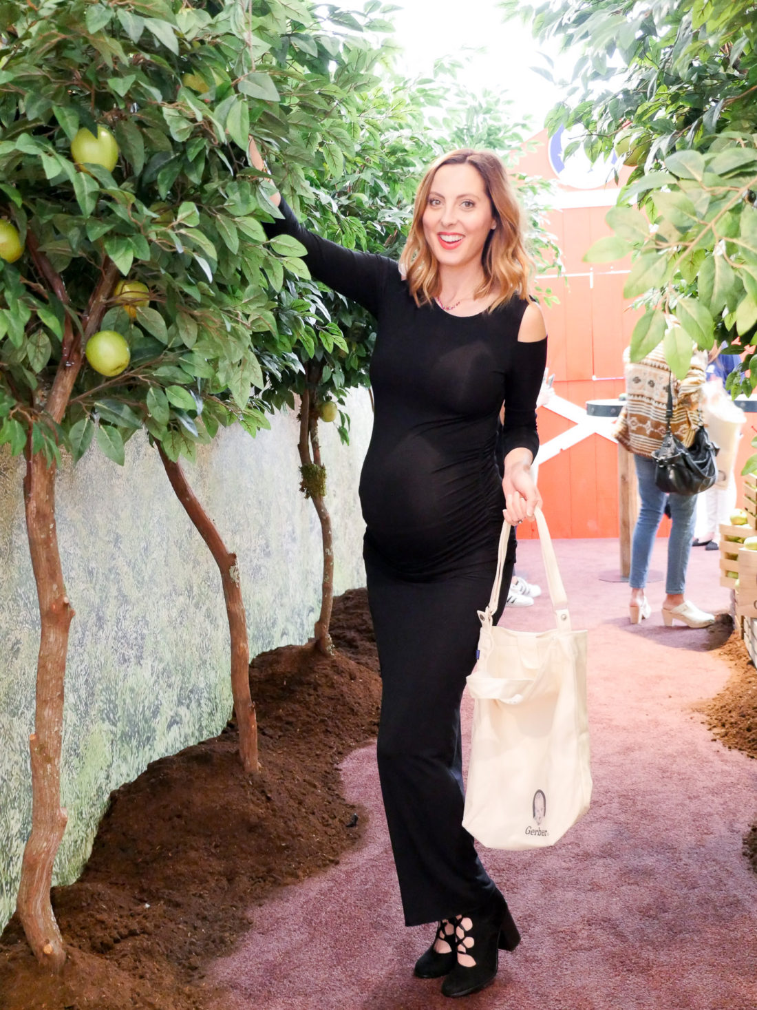 Eva Amurri Martino of lifestyle and motherhood blog Happily Eva After at the Gerber Babies Event in NYC, picking an apple off of a tree in the event's orchard