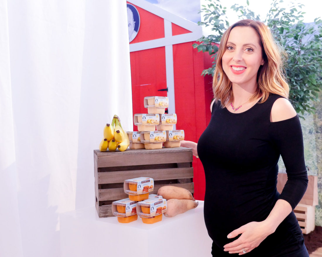 Eva Amurri Martino, cradling her 37 week baby bump in a black Isabella Oliver maternity dress at the Gerber Babies event in NYC