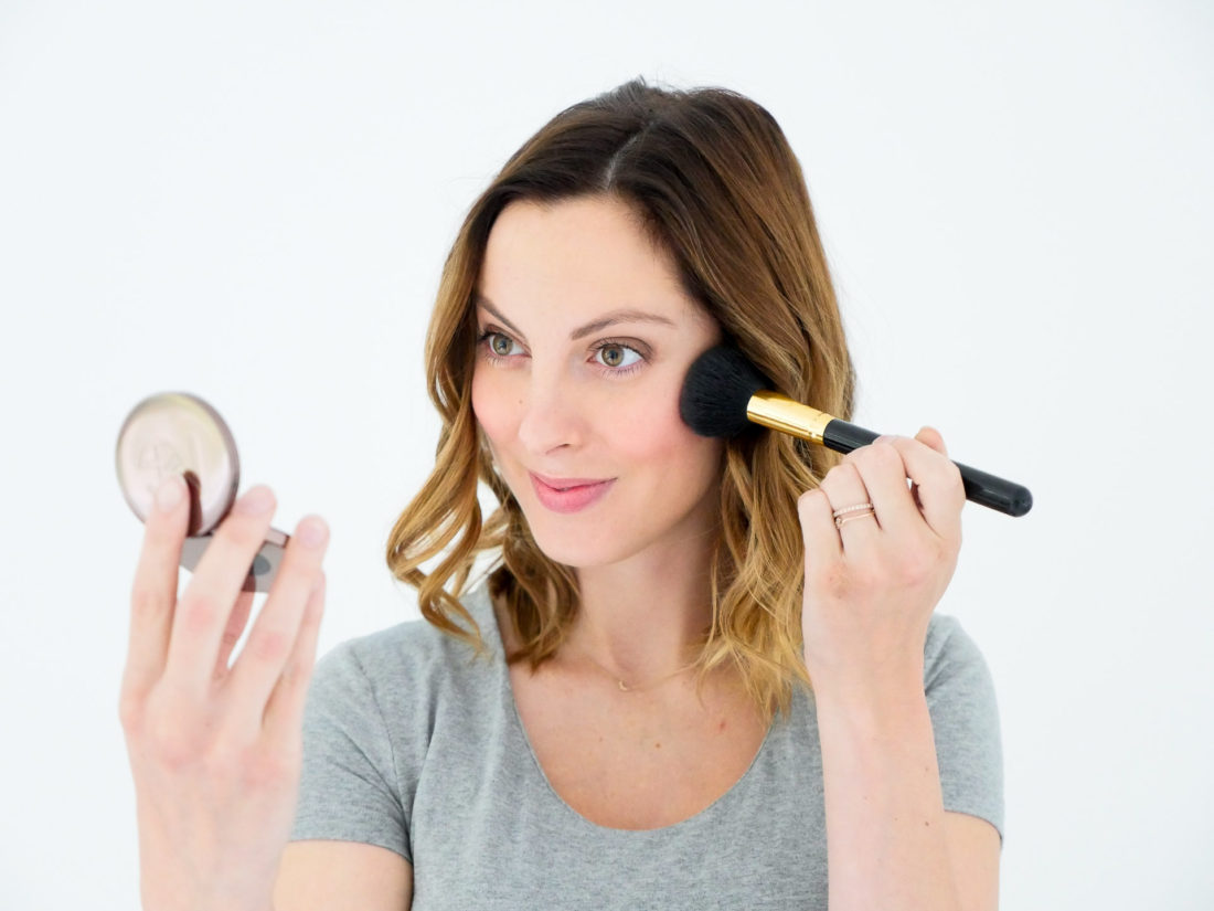 Eva Amurri Martino of lifestyle blog Happily Eva After, applying makeup geek blush in a peachy color to her cheekbones while wearing a grey maternity tshirt at 37 weeks pregnant
