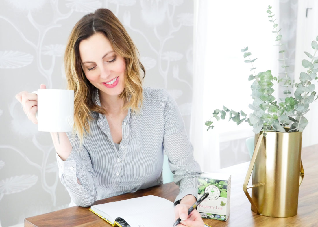 Eva Amurri Martino of lifestyle blog Happily Eva After takes time for herself by writing in a journal and sipping raspberry leaf tea from a white mug in her bright dining room