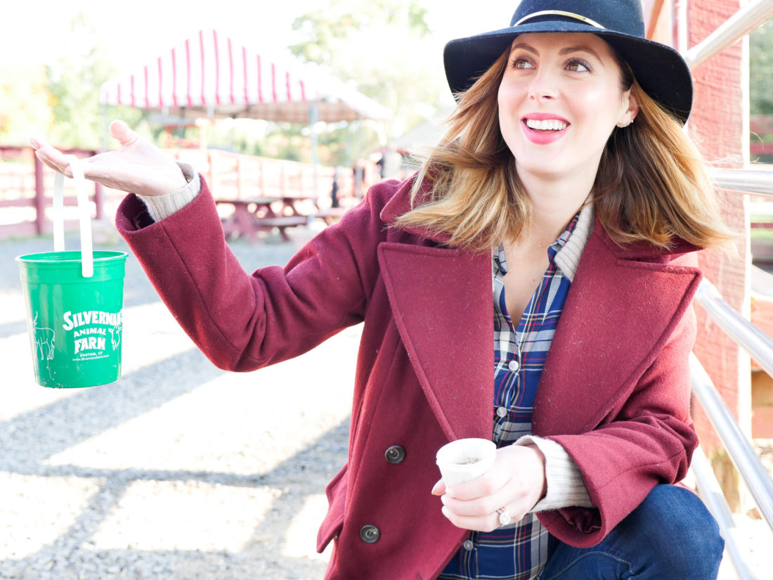 Eva Amurri Martino of lifestyle and motherhood blog Happily Eva After, wearing a plaid shirt and oxblood wool peacoat, holding a feed bucket at Silverman's farm in connecticut