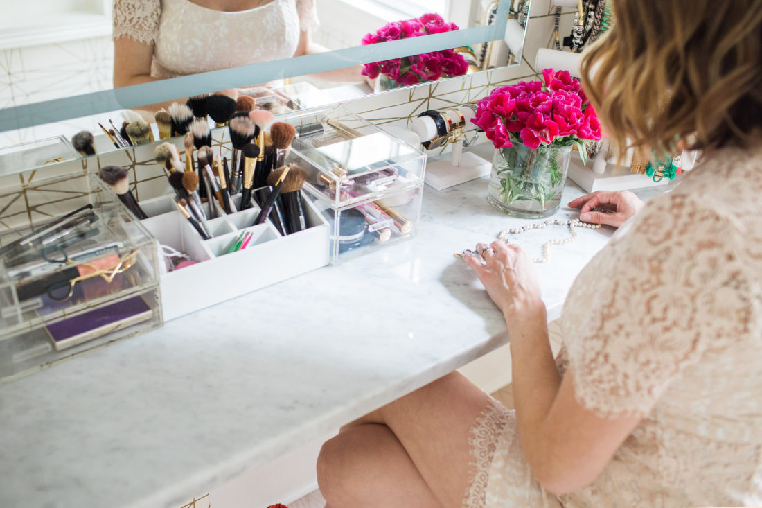 Eva Amurri Martino of lifestyle and motherhood blog happily eva after selects two pearl necklaces to wear from her makeup display in her glam room