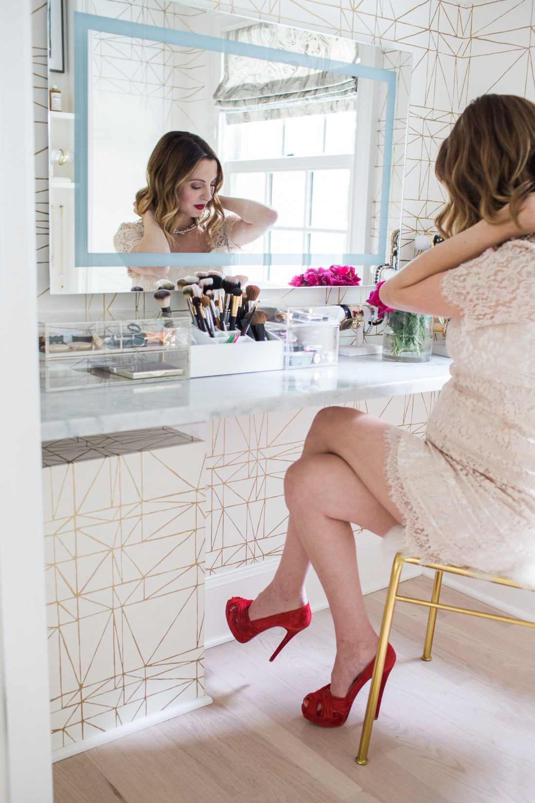 Eva Amurri Martino of lifestyle and motherhood blog Happily Eva After wearing a nude lace maternity dress and sitting at the table in her Glam Room applying makeup and jewelry