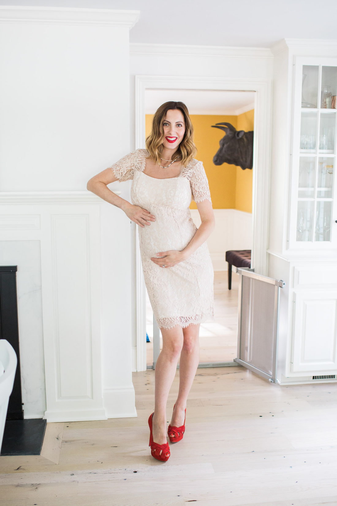 Eva Amurri Martino of lifestyle and motherhood blog happily eva after wears a champagne lace maternity dress at 37 weeks pregnant and stands in red suede louboutin platform pumps next to her fireplace at her home in connecticut