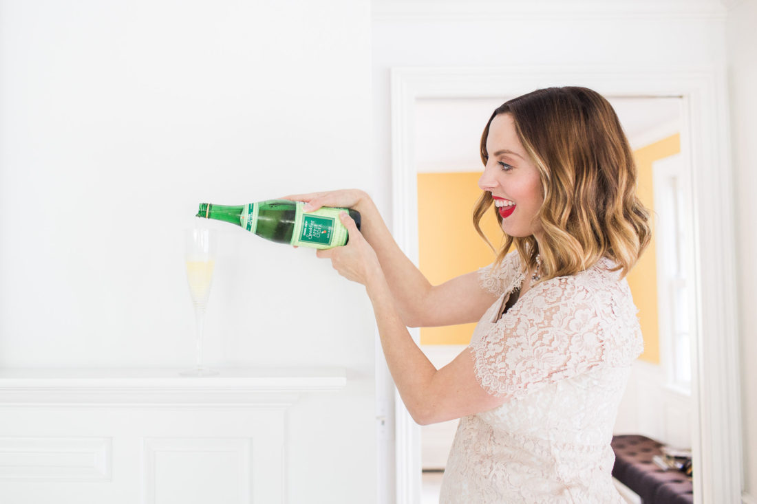 Eva Amurri Martino of lifestyle blog Happily Eva After wearing a champagne colored lace maternity dress and pouring a champagne glass full of sparkling cider