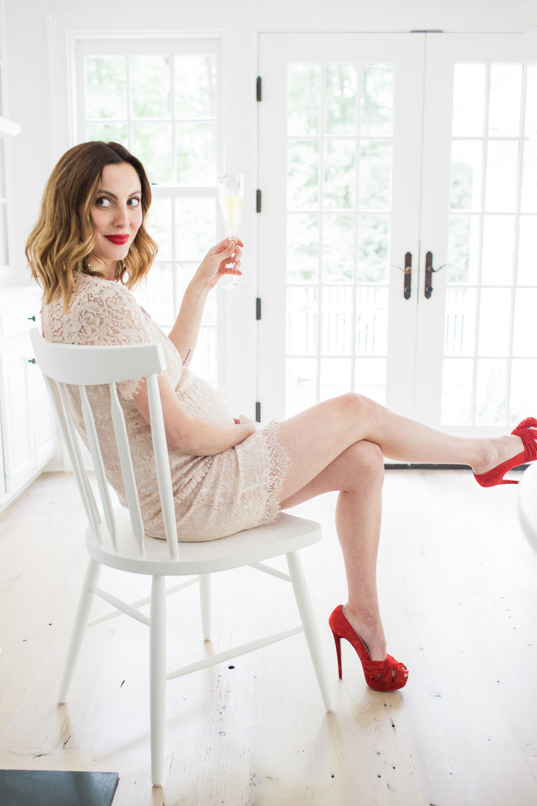 Eva Amurri Martino of lifestyle and Motherhood blog Happily Eva After dressed in a champagne lace maternity dress, red suede Louboutin pumps, and red lipstick, reclining in a white chair and holding a glass of sparkling cider at 37 weeks pregnant
