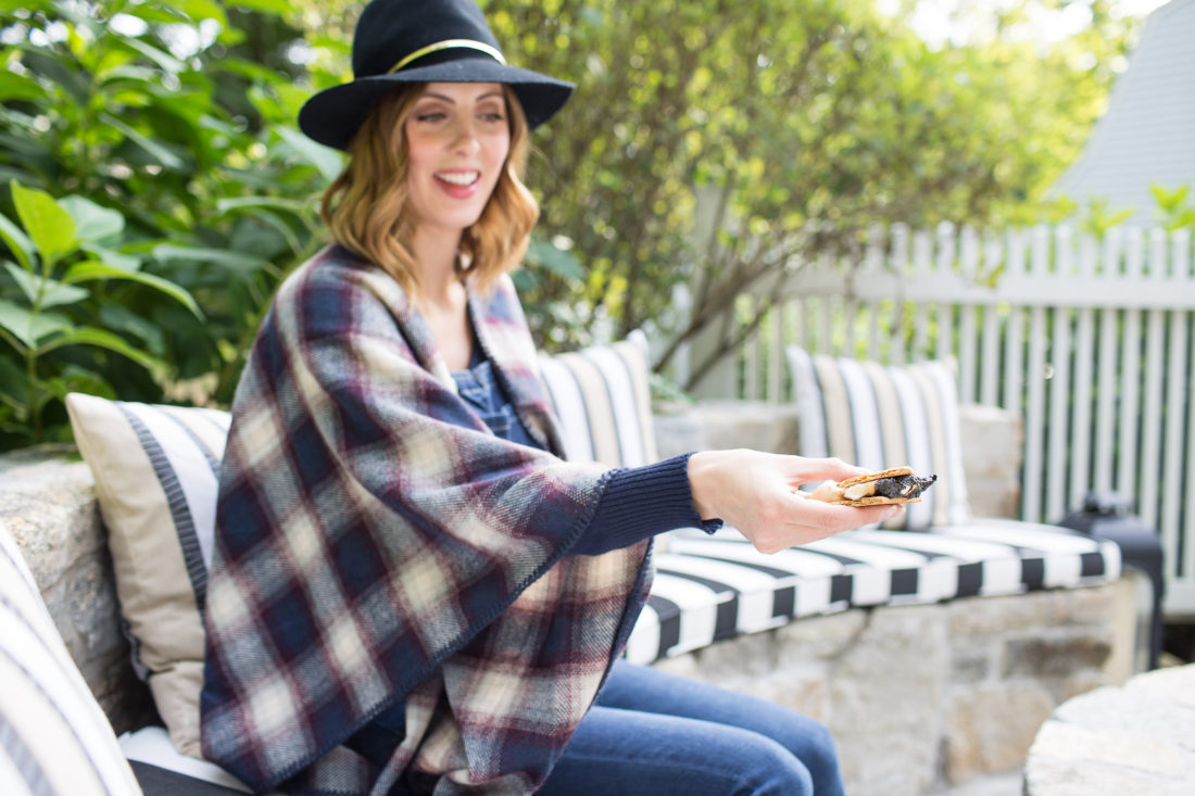 Eva Amurri Martino of lifestyle and motherhood blog Happily Eva After making s'mores at her fire pit while wearing a plaid poncho and navy blue felt hat at 38 weeks pregnant