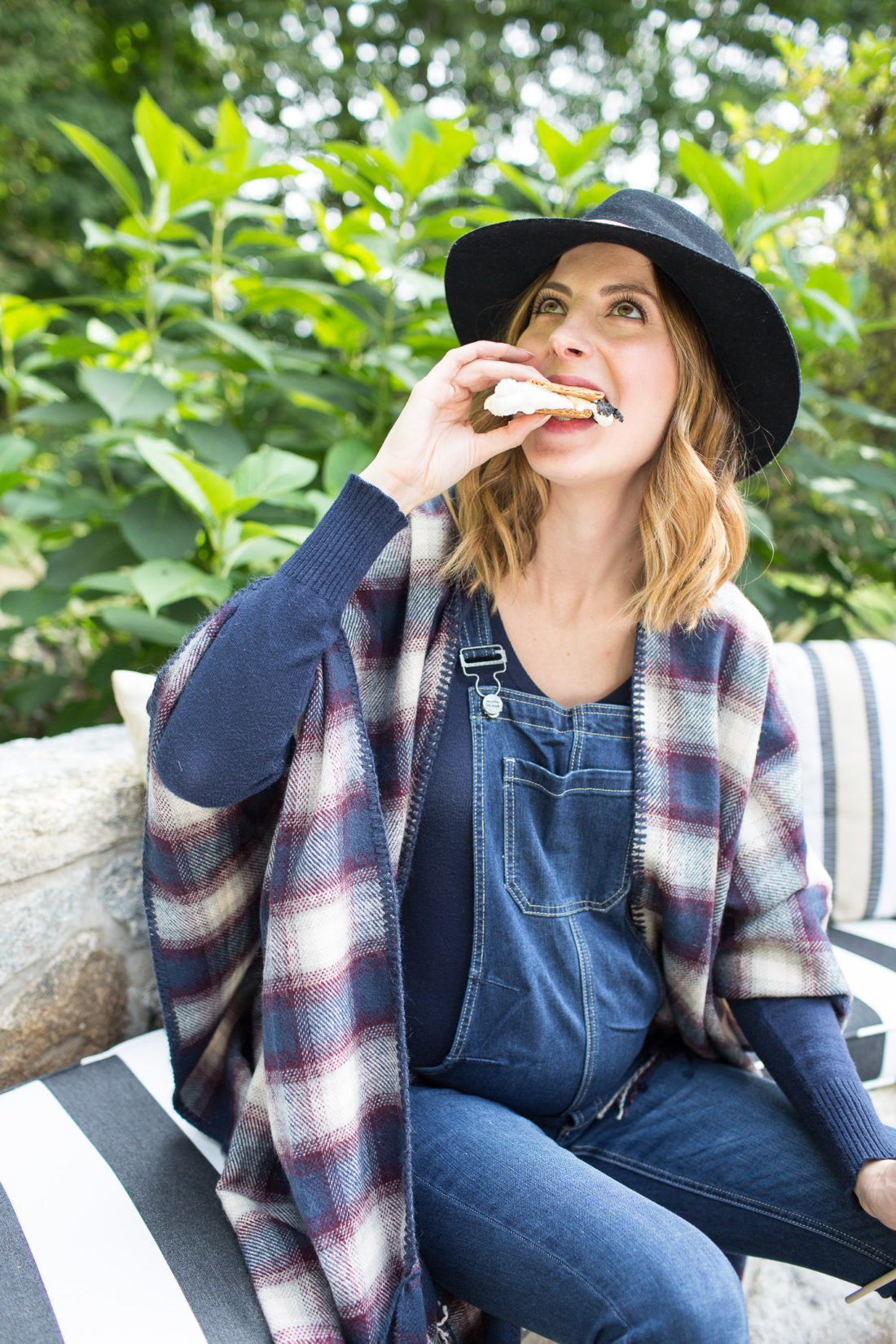 Eva Amurri Martino of lifestyle and motherhood blog Happily Eva After biting in to a S'more at her fire pit while wearing a plaid poncho and navy blue felt hat at 38 weeks pregnant