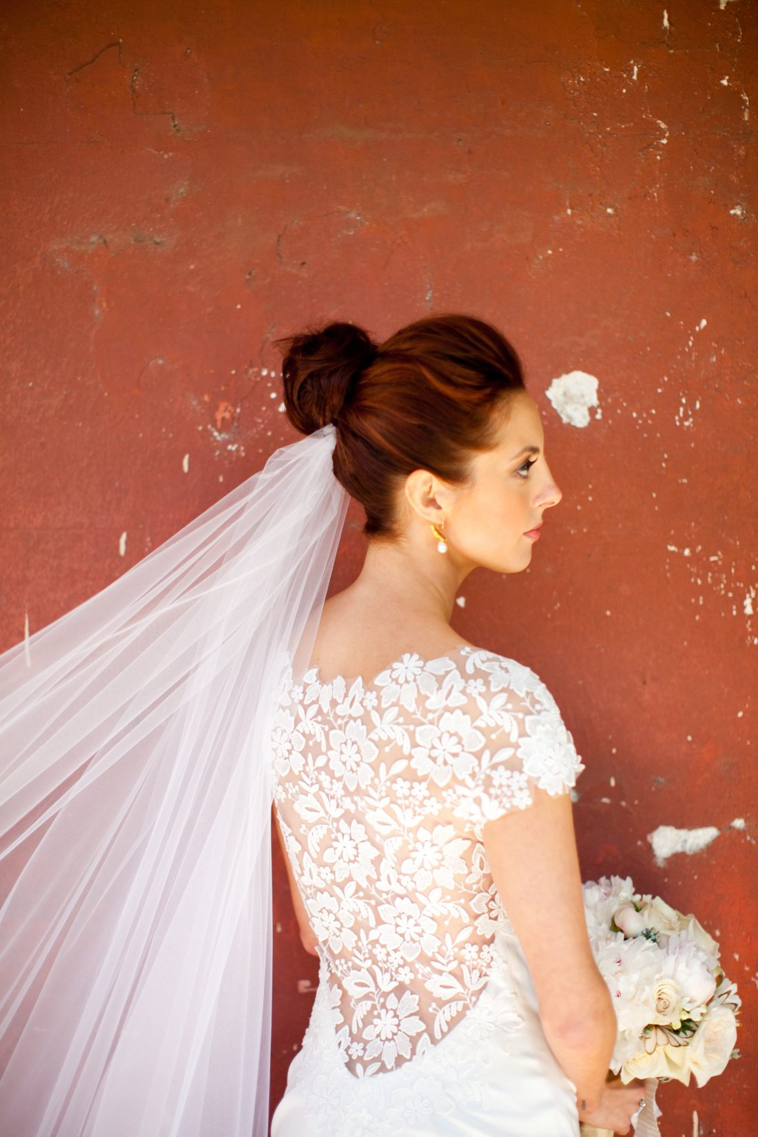 Eva Amurri Martino of lifestyle and motherhood blog Happily Eva After, pictured on her wedding day in 2011 wearing a lela rose wedding dress with flower applique detail on the back, holding a white and blush bouquet