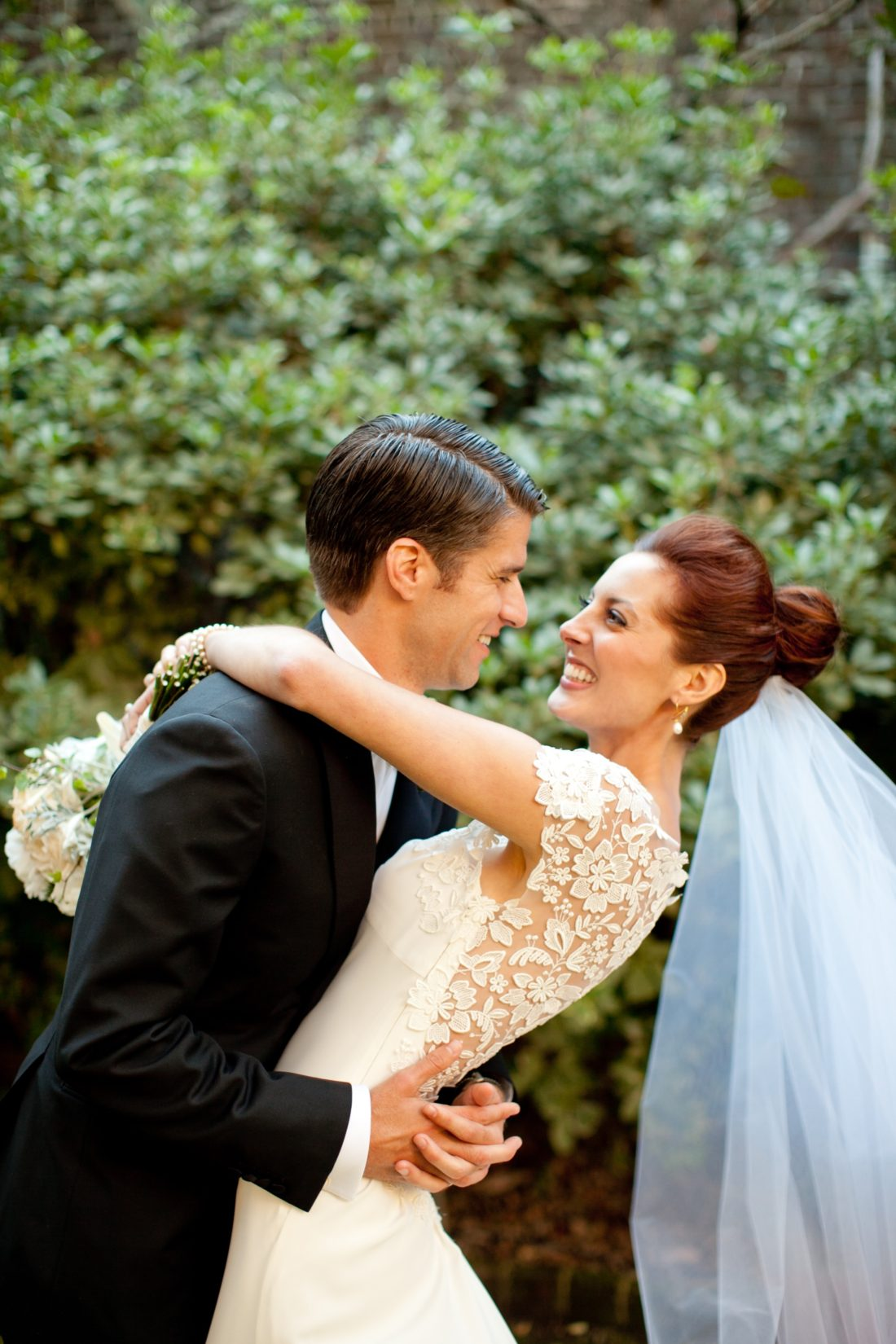 Eva Amurri Martino of lifestyle and motherhood blog Happily Eva After, wearing a white Lela Rose wedding dress with white flower applique detail and a white veil, embracing her husband Kyle Martino wearing a black Brioni tux, on their wedding day in charleston, SC in 2011