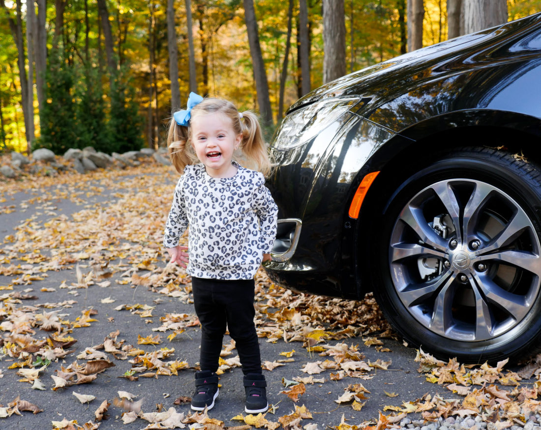 Marlowe Martino pictured wearing a leopard print sweatshirt and black leggings, surrounded by Autumn leaves