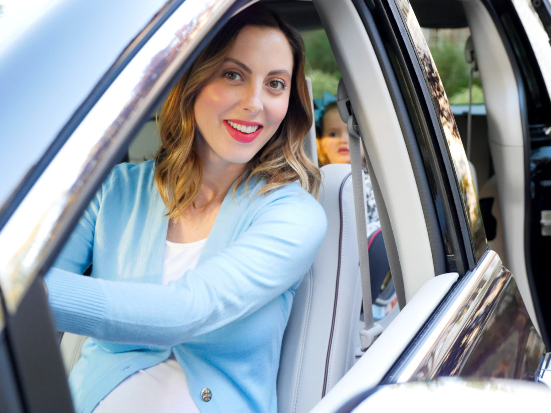 Eva Amurri Martino of lifestyle and Motherhood blog Happily Eva After driving her black Chrysler Pacifica wearing a blue cardigan and white tshirt