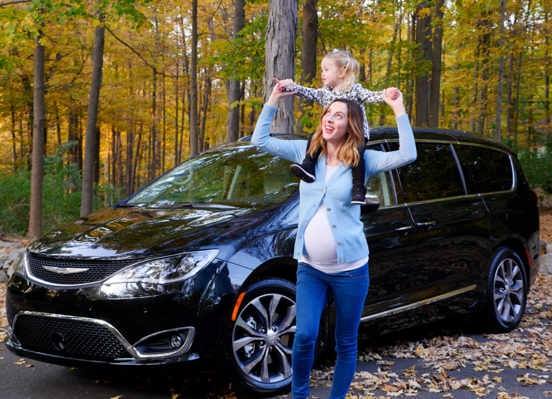 Eva Amurri Martino pictured at nine months pregnant standing in front of her black Chrysler Pacifica with her daughter Marlowe perched on her shoulders