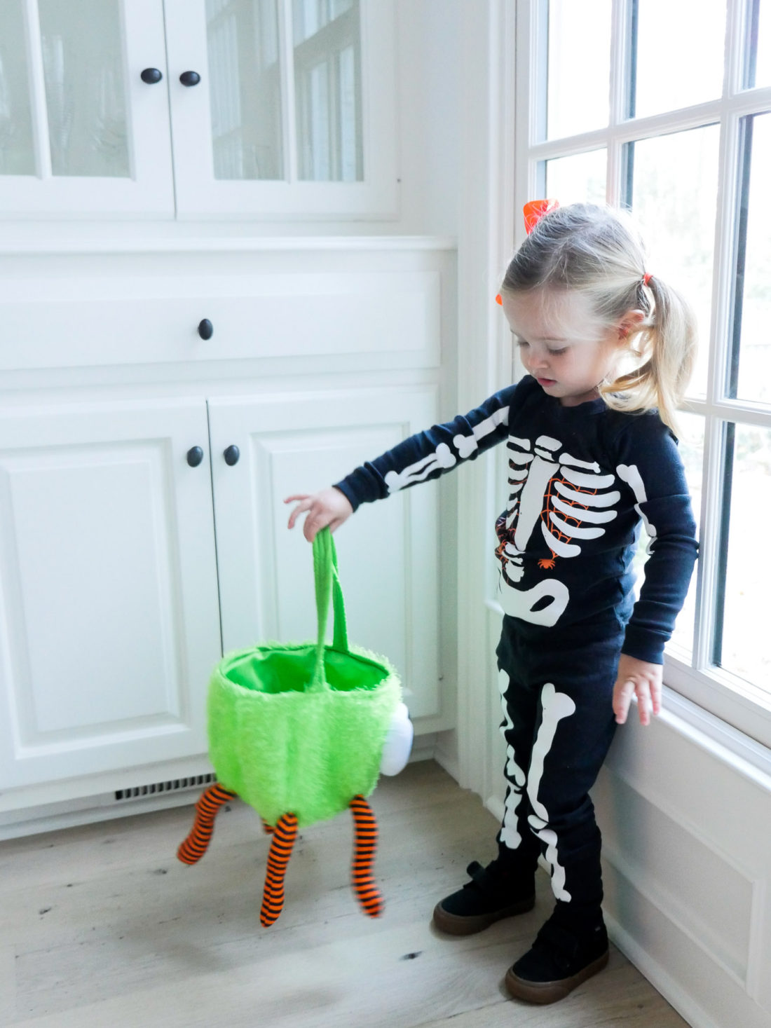 Marlowe Martino dressed up as a skeleton for halloween, holding a green and orange trick or treating bag