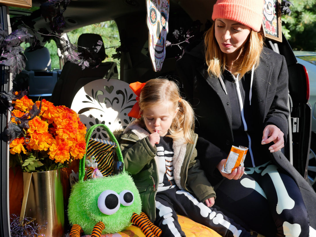 Marlowe Martino eating a snack in the decorated trunk at her school's Trunk Or Treat party