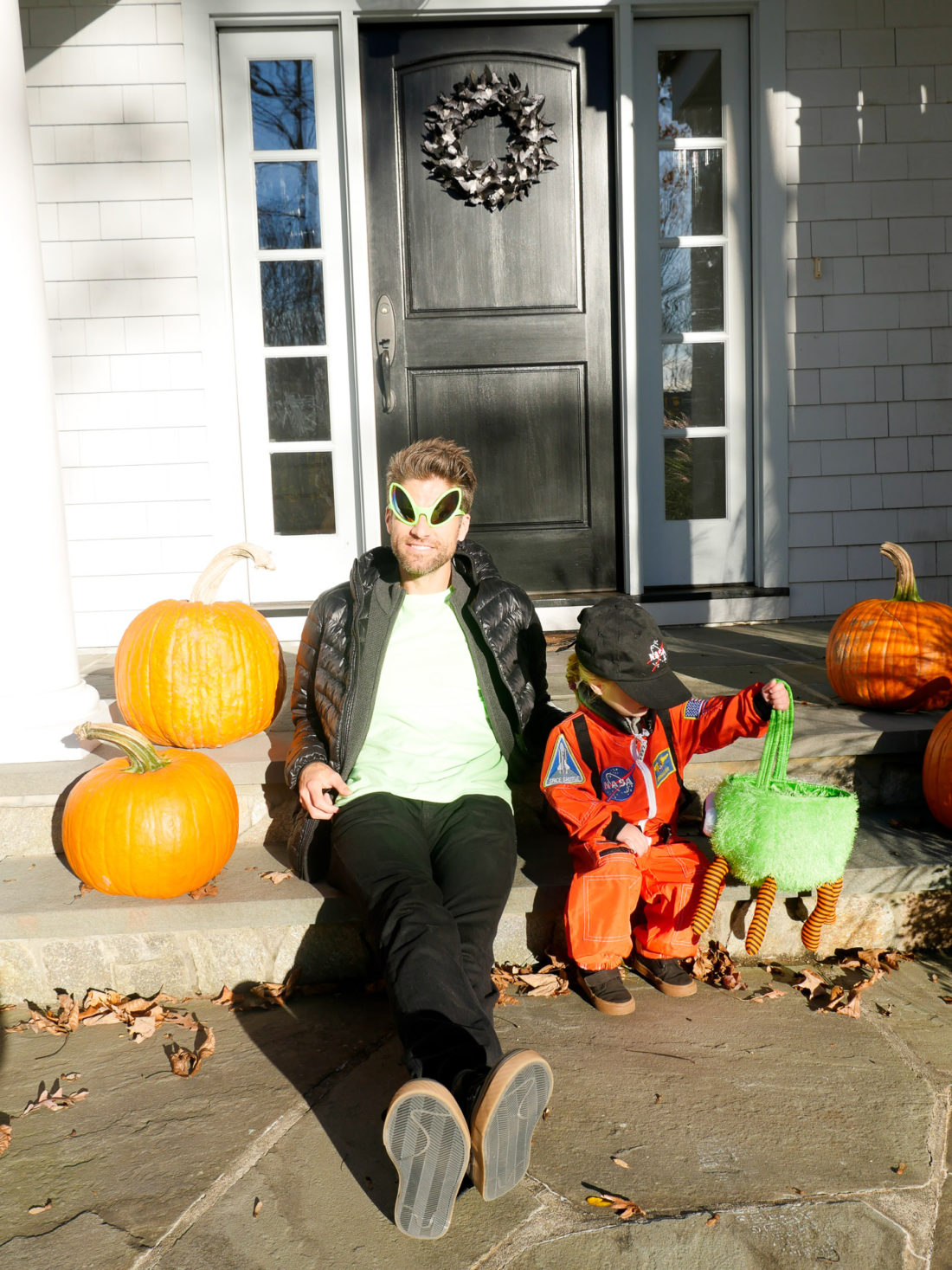 Kyle Martino and Marlowe Martino, sitting on the steps of their Connecticut home dressed as an Alien and an Astronaut for Halloween
