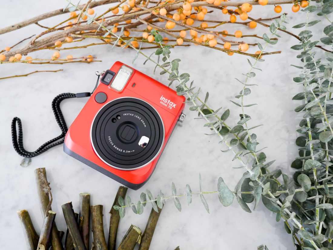 The instax mini 70 camera pictured with the materials to make holiday picture frame place cards for your holiday table, as instructed by lifestyle and motherhood blogger Eva Amurri Martino