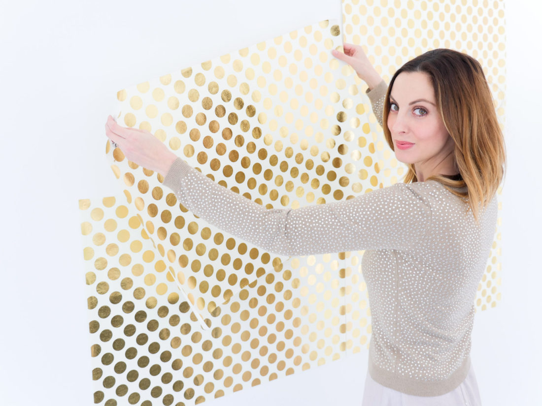 Eva Amurri Martino of lifestyle and motherhood blog Happily Eva After sets up a photo backdrop for her DIY Holiday Photo Place Cards project using the Instax mini 70