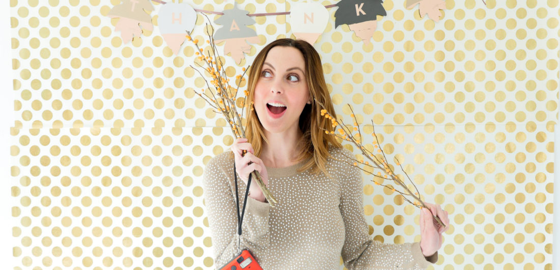Eva Amurri Martino poses in front of her festive Thanksgiving backdrop as part of her DIY Holiday Photo Place Card settings project with Instax mini 70