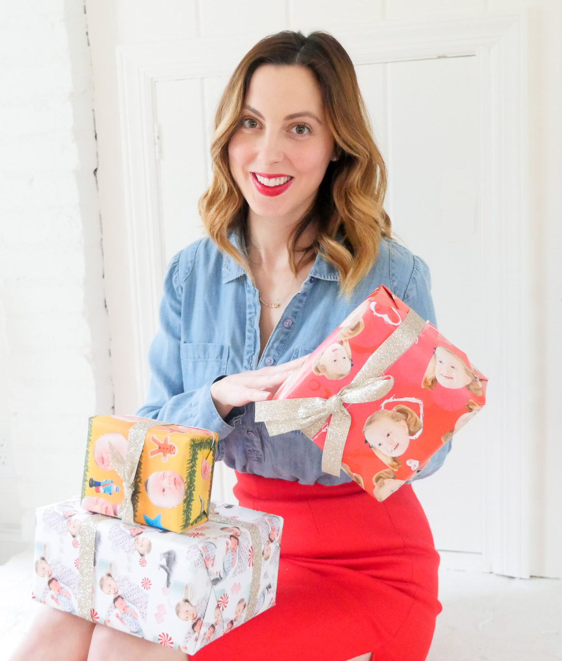 Eva Amurri Martino of lifestyle and motherhood blog Happily Eva After, wearing a red skirt and chambray top and holding wrapped holiday gifts with her children's faces on them